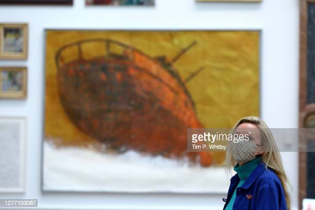 Member of staff inspects works during the press preview of the Summer Exhibition 2020 at The Royal Academy on September 28, 2020 in London, England.
