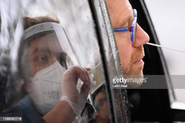 Member of staff is reflected in the car window as Nick Markham, the founder of ExpressTest, takes a PCR swab test at Gatwick Airport on November 27,...