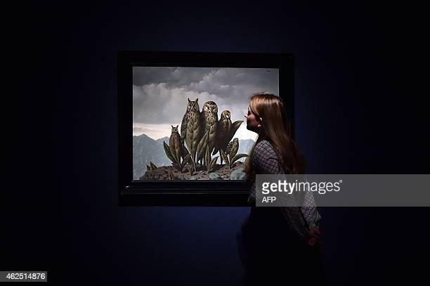 A member of staff looks at a painting by Rene Magritte entitled 'Paysage a Les compagnons de la peur' which is estimatd to fetch 2735 million British...