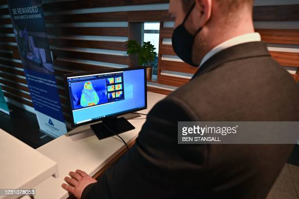 Member of staff looks at a the results of a a thermal imaging camera, as a person waits at the reception desk at the St Giles Hotel near Heathrow...