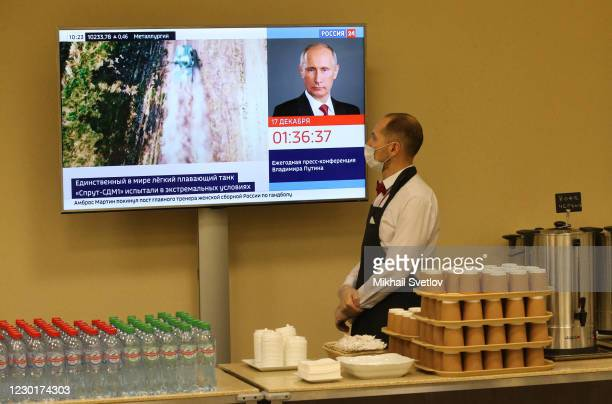 Member of staff looks at the television screen in the hall prior to Vladimir Putin's annual press conference, on December 2020, in Moscow, Russia....
