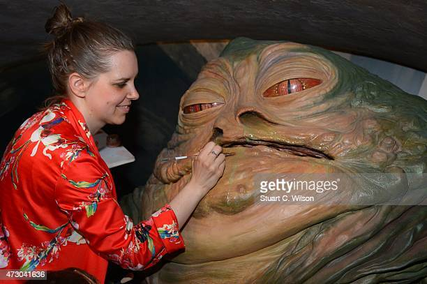 A member of staff makes a last minute touch up of wax figure Jabba The Hut from Star Wars on display at 'Star Wars At Madame Tussauds' on May 12 2015...