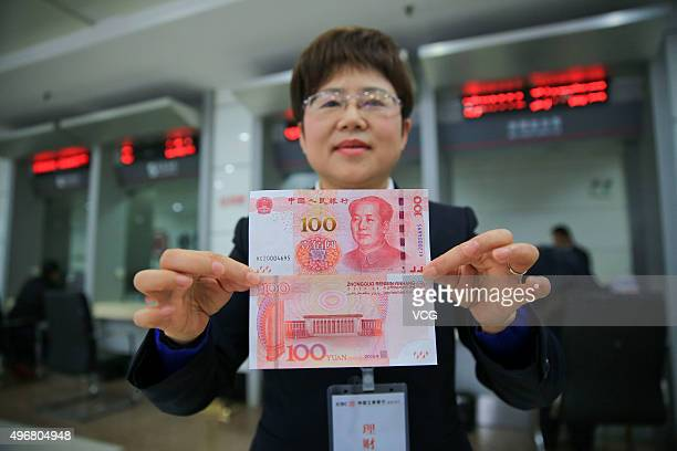 A member of staff of a bank shows both sides of new 100 yuan note on November 12 2015 in Anqing Anhui Province of China The People's Bank of China...