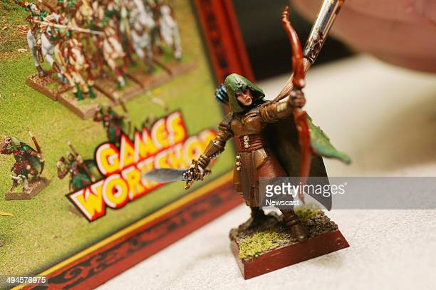 A member of staff paints a figure in a Games Workshop store
