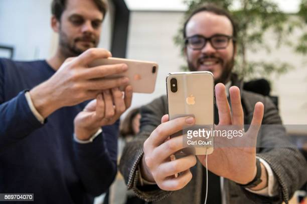 A member of staff photographs a customer as he checks the new iPhone X upon its UK release in the Apple store on November 3 2017 in London England...