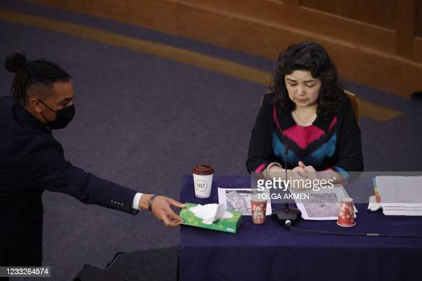 """Member of staff places a box of tissues on the table in front of witness Uyghur teacher Qelbinur Sidik on the first day of hearings at the """"Uyghur..."""