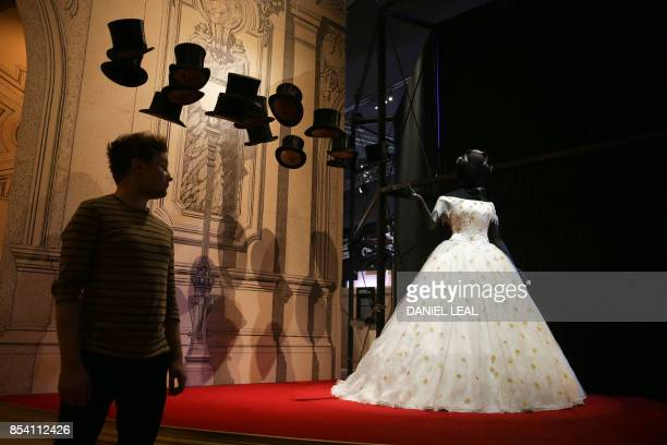 A member of staff poses alongside a dress for Violetta in a production of La Traviata Act I designed by Bob Crowley during a photocall for a new...