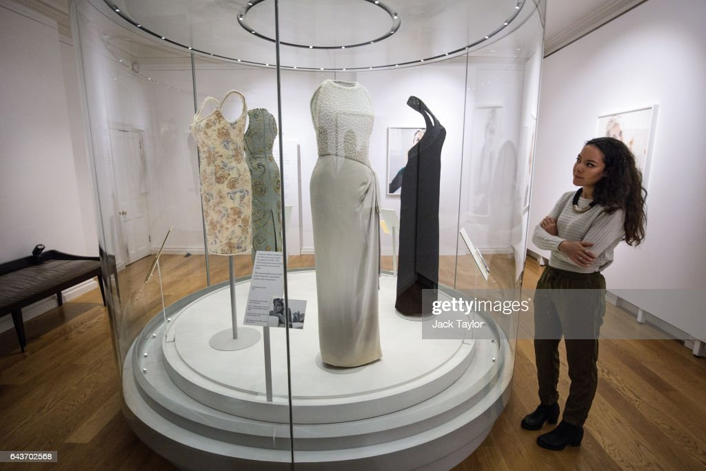 A member of staff poses beside a 1992 Catherine Walker grey silk satin dress with simulated pearl embroidery on the bodice worn by Princess Diana for a photo shoot with Mario Testino for Vanity Fair on display during a press preview at Kensington Palace on February 22, 2017 in London, England. The exhibition 'Diana: Her Fashion Story', which showcases a number of the Princess' dresses and outfits, opens to the public on February 24 as part of events commemorating the life of Princess Diana to mark the 20th anniversary of her death in Paris on August 31st, 1997.