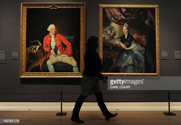A member of staff poses between 1771 portraits by German artist Johan Zoffany entitled George III and Queen Charlotte at the Royal Academy of Arts in...