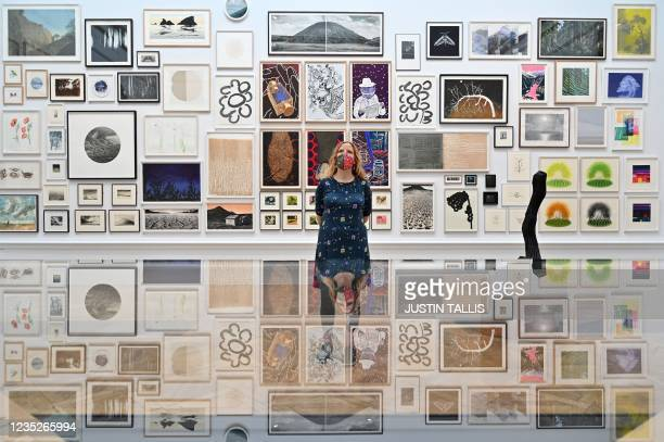 Member of staff poses for a photograph looking at artworks displayed during a press preview for the British Royal Academy of Arts' Summer Exhibition...