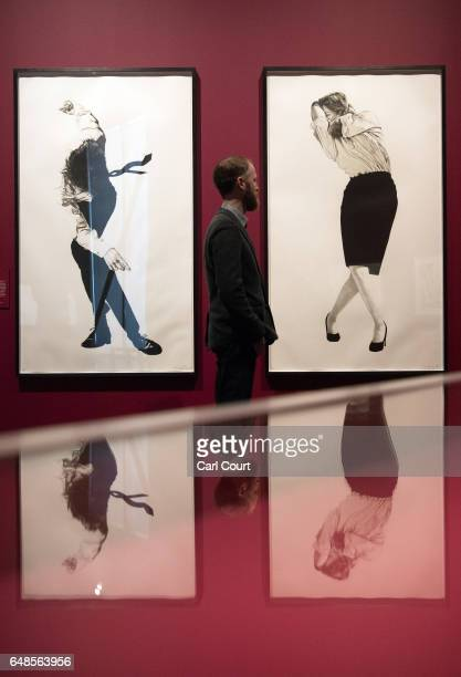 A member of staff poses for photographers next to a pair of lithographs by Robert Longo entitled 'Cindy 1984' and 'Eric 1984' during a press preview...