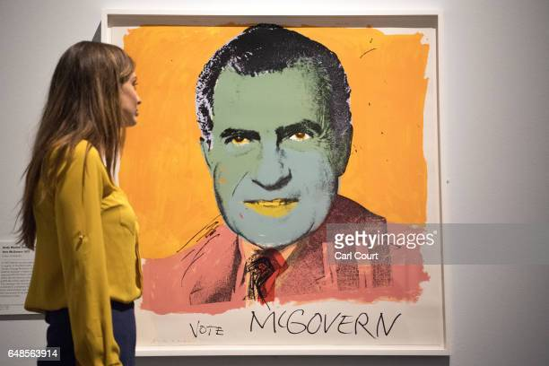 A member of staff poses for photographers next to a work by Andy Warhol entitled 'Vote McGovern 1972' during a press preview for the forthcoming...