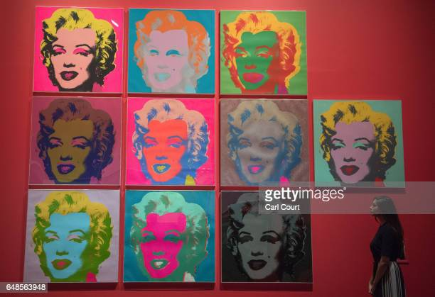 Member of staff poses for photographers next to a work by Andy Warhol entitled 'Marilyn 1967' during a press preview for the forthcoming exhibition...
