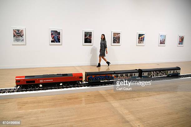 A member of staff poses for photographs next to works by artist Josephine Pryde including 'The New Media Express in a Temporary Siding ' during a...