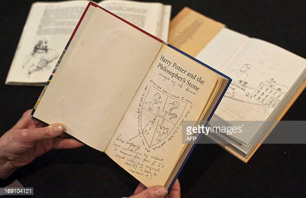 A member of staff poses holding a first edition copy of 'Harry Potter and the Philosopher's Stone' by British author J K Rowling annotated by Rowling...