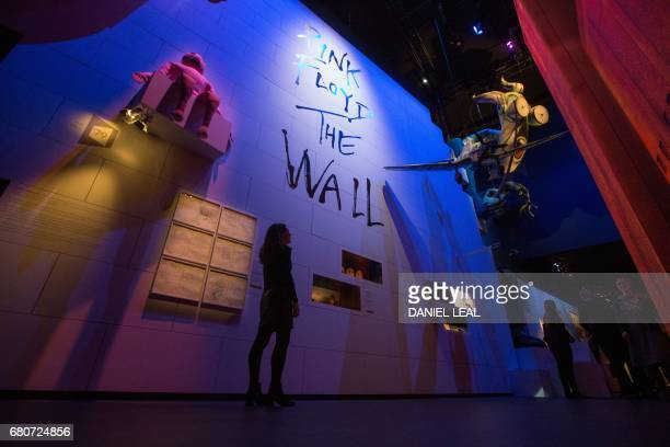 A member of staff poses in front of an artwork installation 'The Wall' during a photocall at the 'The Pink Floyd Exhibition Their Mortal Remains' at...