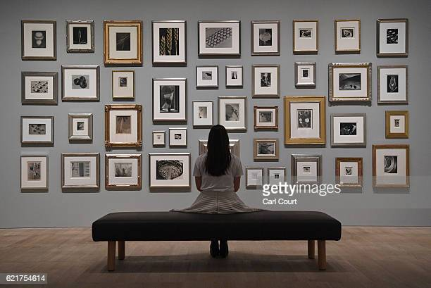"""Member of staff poses infront of photographs belonging to Elton John during a press preview for """"The Radical Eye: Modernist Photography from The Sir..."""