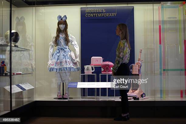 A member of staff poses next to a display featuring a doll titled 'Sweet Ensemble by Baby the Stars Shine Bright' dating from 201112 and a Hello...