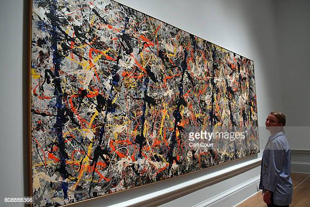 A member of staff poses next to a painting by US artist Jackson Pollock entitled 'Blue Poles' at the Royal Academy of Arts on September 20 2016 in...