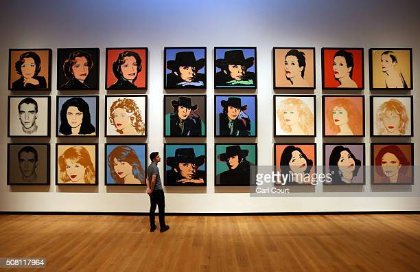 A member of staff poses next to a series of artworks by Andy Warhol at the Ashmolean Museum on February 2 2016 in Oxford England The work forms part...