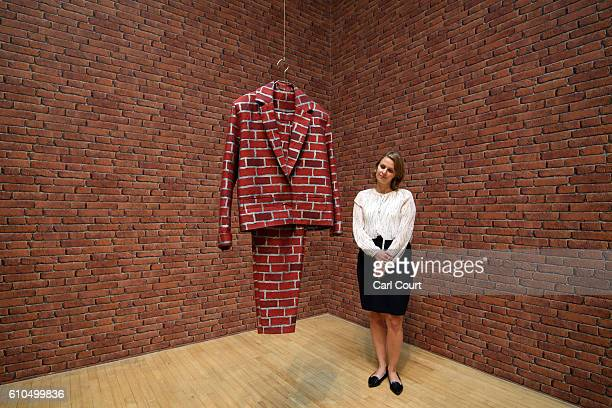 A member of staff poses next to an installation by British artist Anthea Hamilton entitled 'Brick Suit' during a press preview for the 2016 Turner...