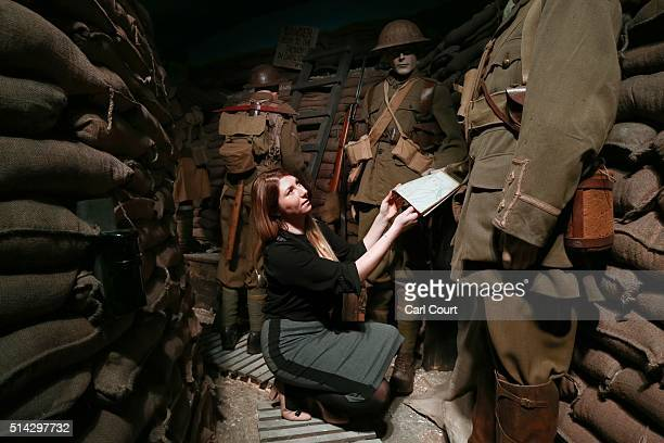 A member of staff poses next to British World War One soldiers in a recreated trench during a press preview for the 'Remembering 1916 Life on the...