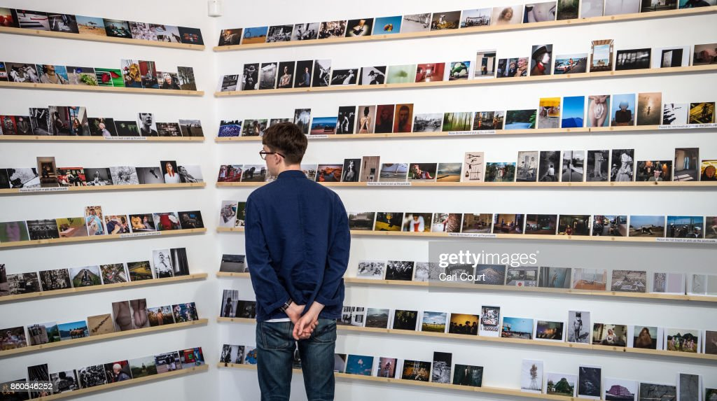 A member of staff poses next to photograph postcards featuring images by photographers including Martin Parr and Wolfgang Tillmans ahead of a secret raffle at ThePrintSpace gallery on October 12, 2017 in London, England. The photographs will be on display from October 12- 24 and will be raffled on October 30 with all the money raised going to the Hepatitis C Trust's campaign to eliminate hepatitis C from the UK by the year 2030.