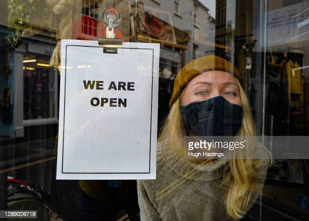 "Member of staff poses next to the ""We Are Open"" sign in the Finisterre clothing shop, which has re-opened today, on December 2, 2020 in Falmouth,..."