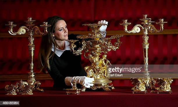 A member of staff poses with a Centrepiece during a photocall to showcase items from the Royal Collection used during state banquets in Buckingham...
