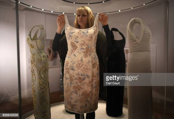 A member of staff poses with a dress designed by Catherine Walker which Princess Diana wore to a Christies Auction Gala in New York in 1997 during a...