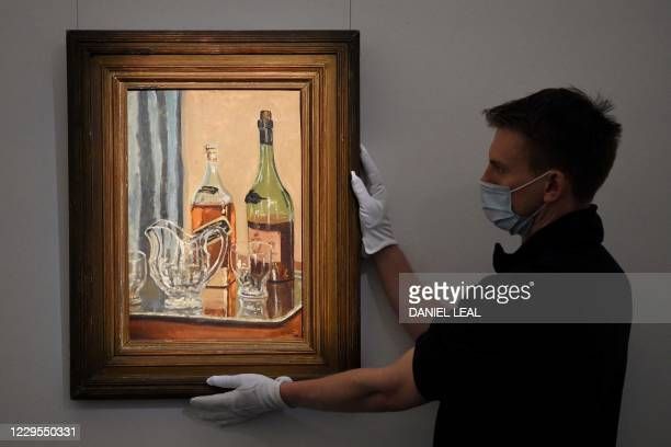 "Member of staff poses with a painting by Britain's former prime minister Winston Churchill entitled ""Jug with Bottles"" at Sotheby's auction house in..."