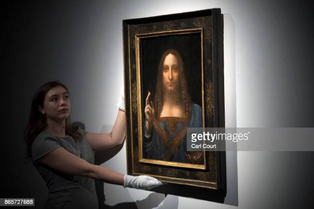 A member of staff poses with a painting by Leonardo da Vinci entitled 'Salvator Mundi' before it is auctioned in New York on November 15 at Christies...