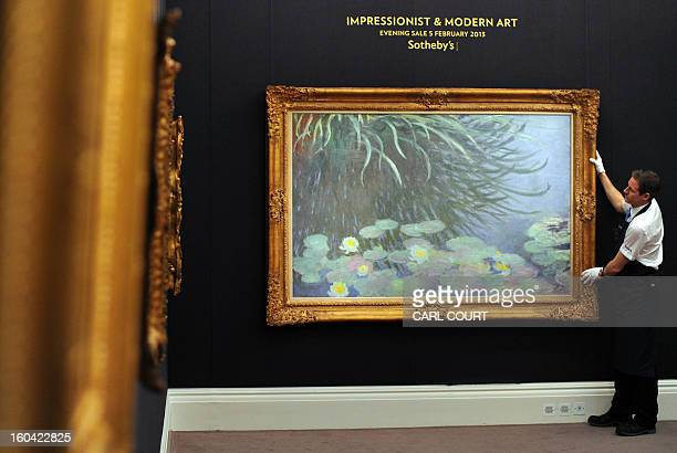 A member of staff poses with a painting entitled 'Nympheas avec reflets de hautes herbes' by French artist Claude Monet at Sotheby's auction house in...