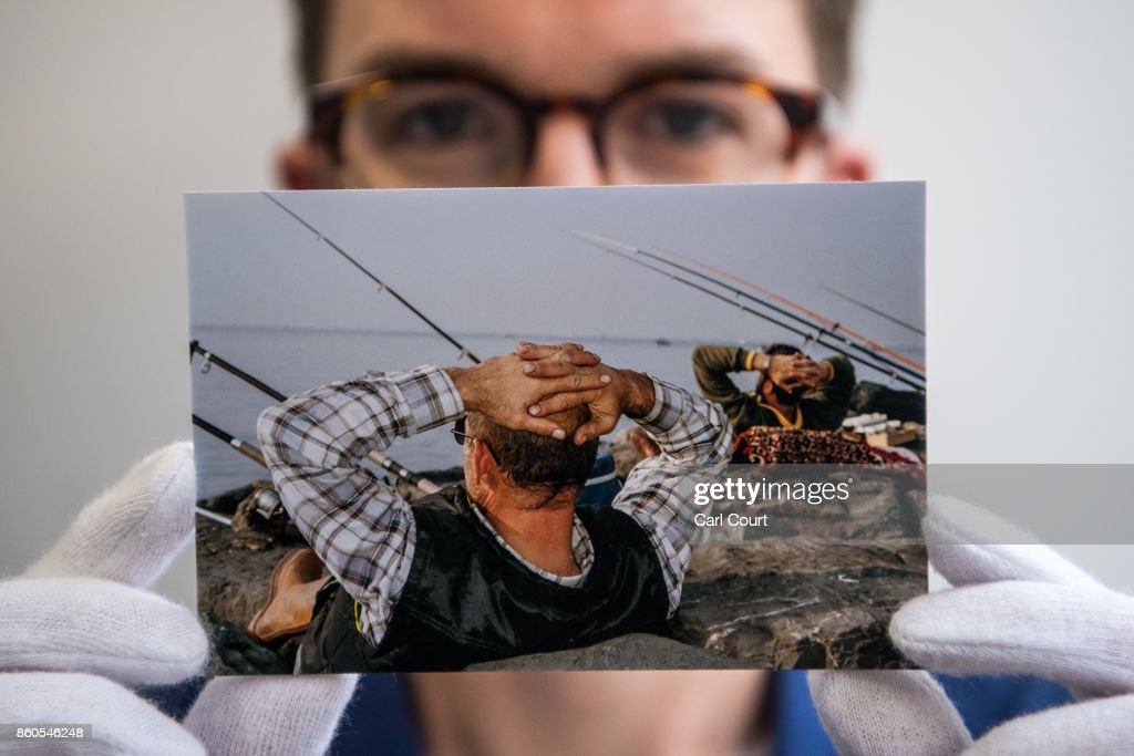 A member of staff poses with a postcard featuring a photograph by Martin Parr ahead of a secret raffle at ThePrintSpace gallery on October 12, 2017 in London, England. The photographs will be on display from October 12- 24 and will be raffled on October 30 with all the money raised going to the Hepatitis C Trust's campaign to eliminate hepatitis C from the UK by the year 2030.
