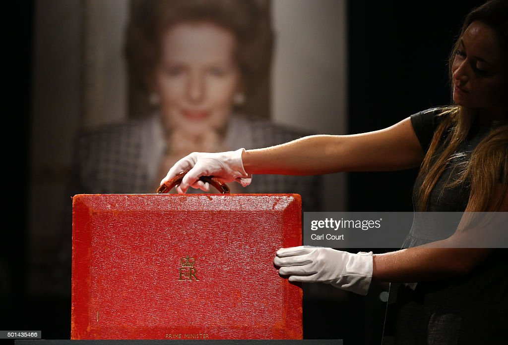 A member of staff poses with a 'Prime Ministerial Red Morocco Dispatch Box' during a press preview at Christies auction house on December 15, 2015 in London, England. Due to form part of the 'Mrs Thatcher - Property from the Collection of The Right Honourable The Baroness Thatcher of Kesteven LG, OM, FRS' sale on December 15th, it is expected to fetch between 3,000-5,000 GBP