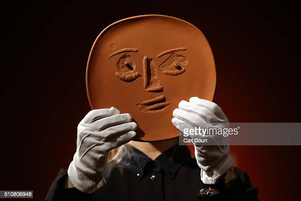 A member of staff poses with an unglazed terracotta plate entitled 'Visage aux grands yeux' by Pablo Picasso at Christie's auction house on February...