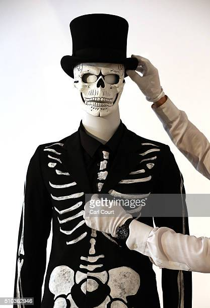 A member of staff poses with James Bond's Day of the Dead Costume worn by Daniel Craig in Spectre during a photocall at Christie's auction house on...