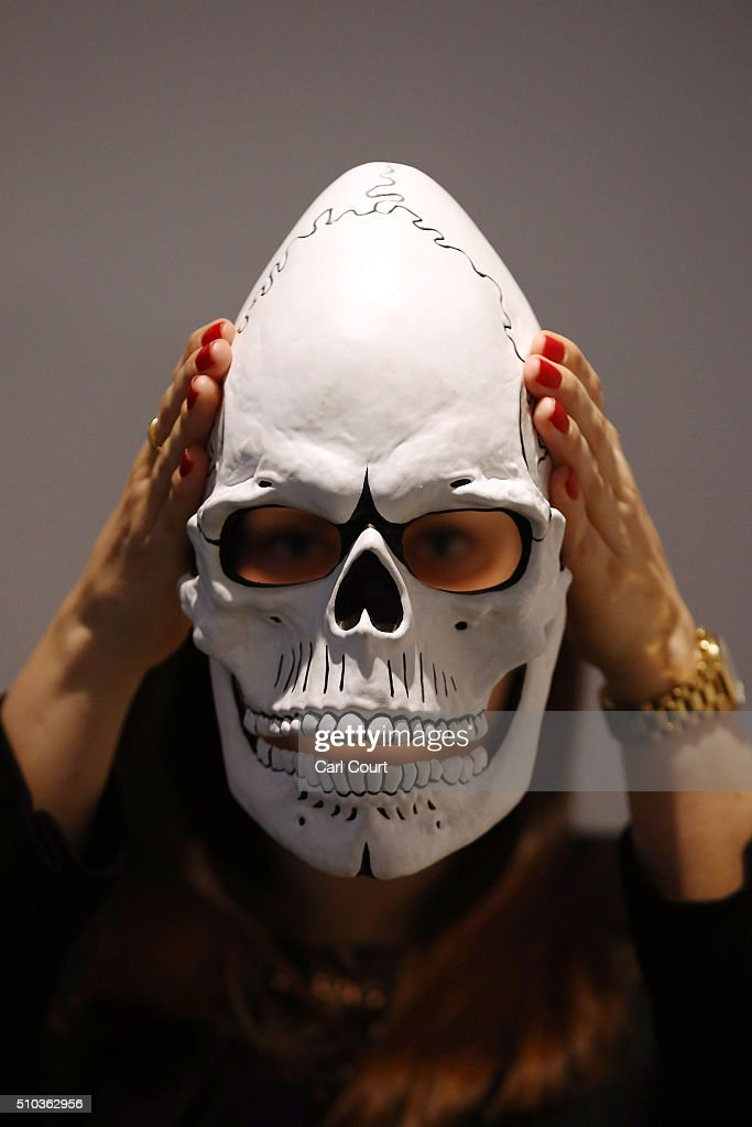 A member of staff poses with the mask from James Bond's Day of the Dead Costume, worn by Daniel Craig in Spectre, during a photocall at Christie's auction house on February 15, 2016 in London, England. Forming part of the 'James Bond Spectre - The Auction' sale on 18th February it is expected to fetch between 12,000 - 18,000 GBP.