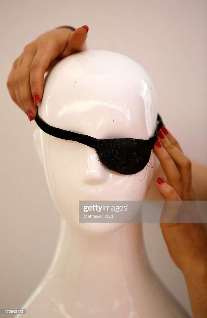 A member of staff prepares an eye patch, worn by John Wayne during the film True Grit, for sale at Christie's South Kensington on June 19, 2013 in London, England. The item is part of an auction entitled 'Pop Culture' featuring memorabilia charting the history of cinema, pop and rock and roll.