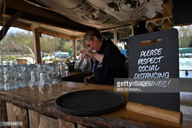 Member of staff prepares an outdoor bar in the beer garden of the Halfway House pub in Brenchley, south east England, on April 9 ahead of the easing...