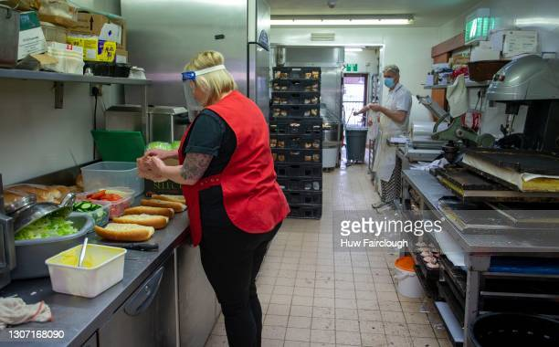 Member of staff prepares baguettes in the kitchen of the Cottage Loaf Bakery on March 15, 2021 in Blackwood, Wales. The bakery has remained open...