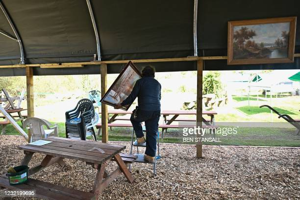 Member of staff prepares to hang a painting in a covered outdoor seating area in the beer garden of the Halfway House pub in Brenchley, south east...