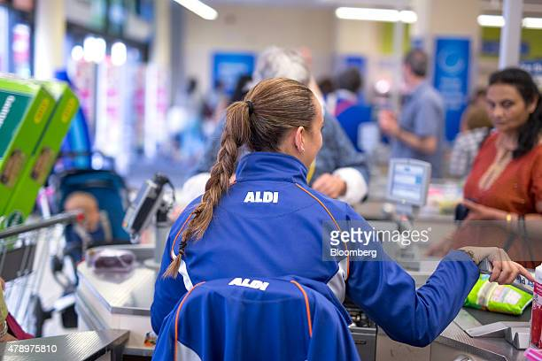 A member of staff prepares to scan goods taken from a customer's shopping basket at the checkout counter inside an Aldi supermarket store in London...