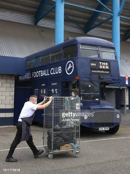 Member of staff pushes a trolley past a Millwall FC branded bus outside the stadium prior to the Sky Bet Championship match between Millwall and...