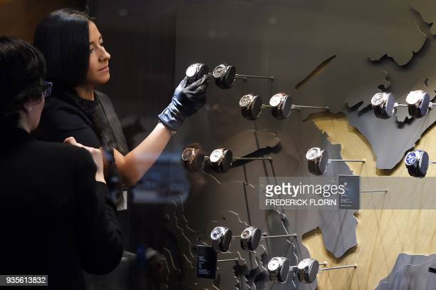 A member of staff puts watches on display on March 21 2015 at the stand of Swiss watchmaker Bucherer during the press day of Baselworld watch and...