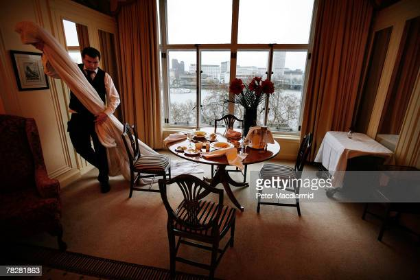 A member of staff removes net curtains for cleaning from the Monet Suite at the Savoy Hotel on December 6 2007 in London Some of the fixtures and...