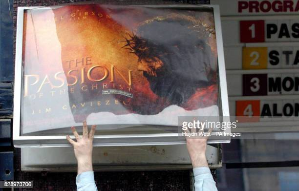 A member of staff replaces the billboard with the poster of Mel Gibson's new film 'The Passion of the Christ' at the Savoy cinema in Dublin Ireland...