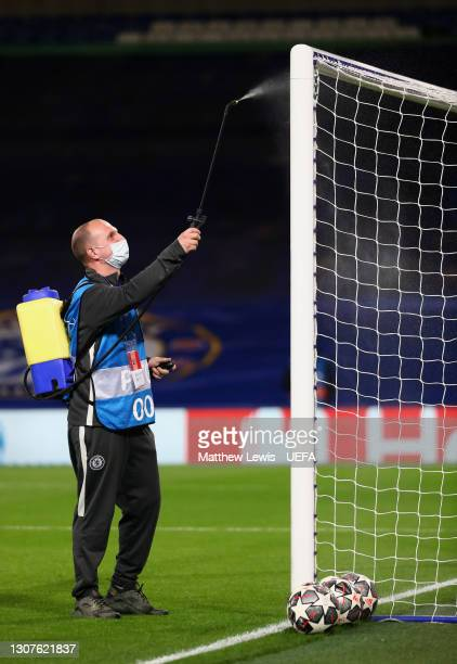 Member of staff sanitises goalposts prior to the UEFA Champions League Round of 16 match between Chelsea FC and Atletico Madrid at Stamford Bridge on...