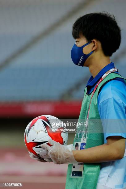 Member of staff sanitises the match ball during the Women's First Round Group F match between China and Brazil during the Tokyo 2020 Olympic Games at...