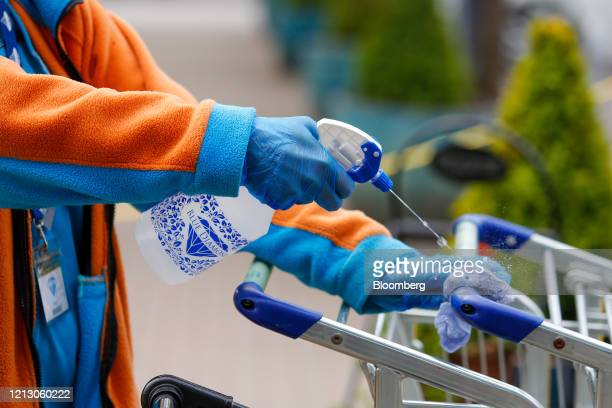 Member of staff sanitizes shopping trolley handles at the Grosvenor Garden Centre, operated by Blue Diamond Ltd., in Belgrave, U.K., on Friday, May...
